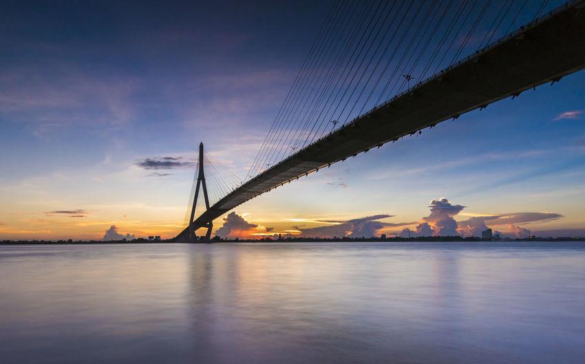 Silhouette bridge over sea against orange sky during sunset