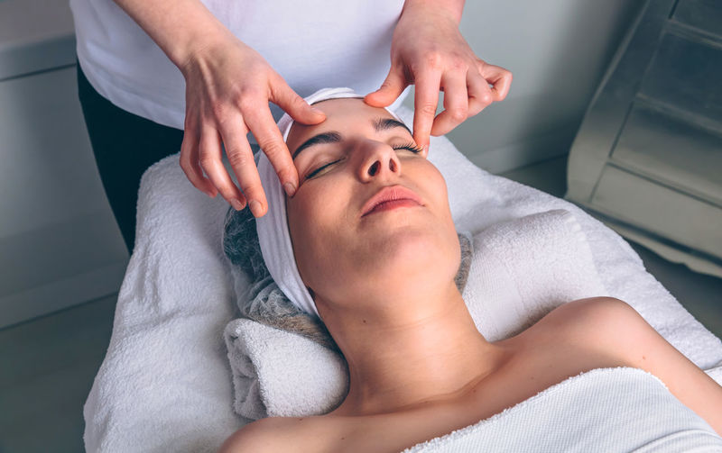 Massage therapist treating customer at spa