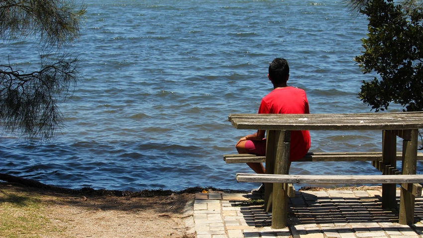 enjoying the beauty of nature Nature Water Alone Boy Red Red Tshirt Rear View Water Sitting One Person Red Real People Day Sea Outdoors Leisure Activity Nature