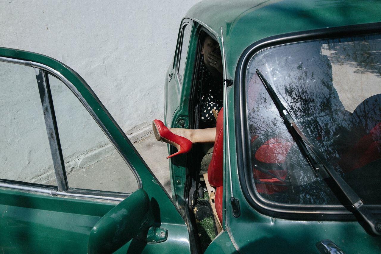 Women sitting in green vintage car against wall