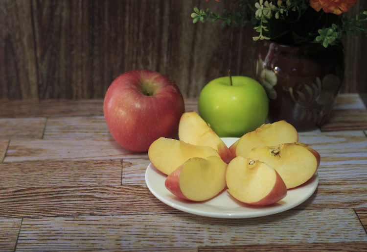 Red and green apples on the wooden floor. Apple Apple - Fruit Close-up Focus On Foreground Food Food And Drink Freshness Fruit Granny Smith Apple Group Of Objects Healthy Eating Indoors  No People Red SLICE Still Life Table Variation Wellbeing Wood - Material