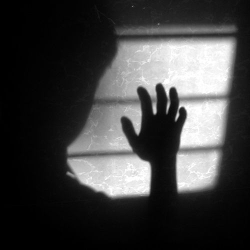 Shadow of person hand on window