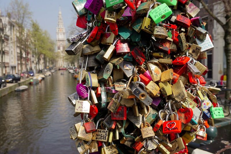 Close-up of padlocks on bridge over river in city