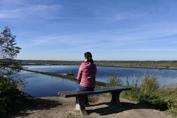 Rear view of woman sitting on bench by lake against sky