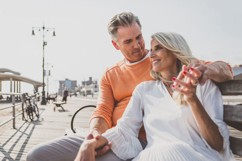 Smiling couple sitting on bench against sky during sunny day