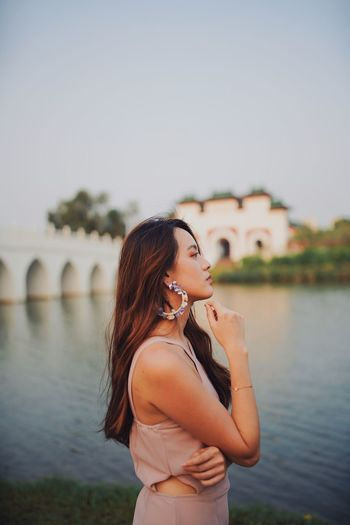 Woman looking away while standing by river