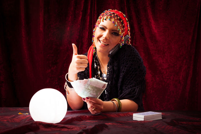 Studio shot of fortune teller who made lots of money telling you what you wanted to hear. Crystal Ball Forecast Fortune Teller Fortune Telling Future Liar Money Paranormal Portrait Psychic Medium Red Rich Scheme Studio Shot Woman Women Young Women