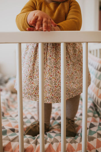 Yellow Crib Baby Child Daughter Childhood Dress Family Matters Family With One Child Lifestyles Girl Casual Clothing Day Chair Finger Focus On Foreground Furniture Low Section Home Interior Human Body Part Standing Hand One Person Indoors  Real People
