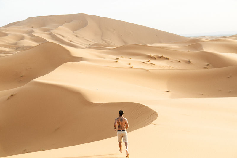 Rear View Of Man Running In Desert