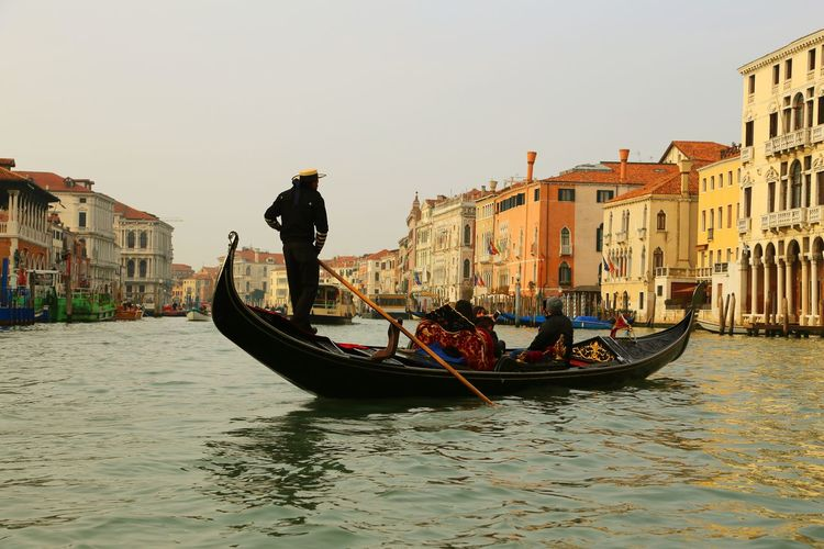People in gondola on grand canal against sky in city