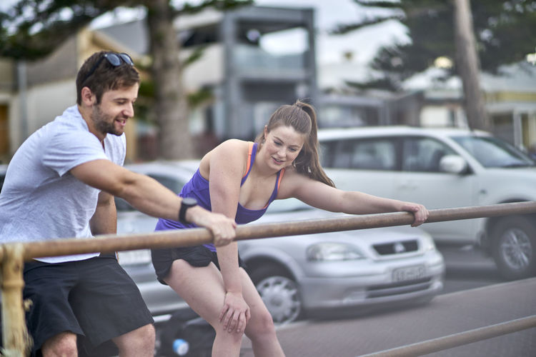 Athlete Coach Couple Car City Day Focus On Foreground Friendship Happiness Leisure Activity Lifestyles Outdoors Real People Smiling Sport Sports Clothing Togetherness Training Two People Workout Young Adult Young Men Young Women