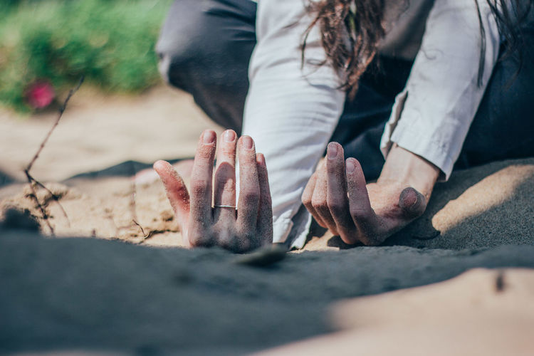 Close-up of woman hands on sand