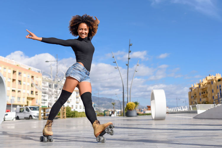 Young fit black woman on roller skates riding outdoors on urban street. Smiling girl with afro hairstyle rollerblading on sunny day Fun Happy Roller Beautiful Woman Happiness Leisure Activity Lifestyles Looking At Camera One Person Outdoors People Portrait Real People Rollerblading Rollerskating Skater Skatergirl Skates Skating Sky Smiling Sport Sports Young Adult Young Women