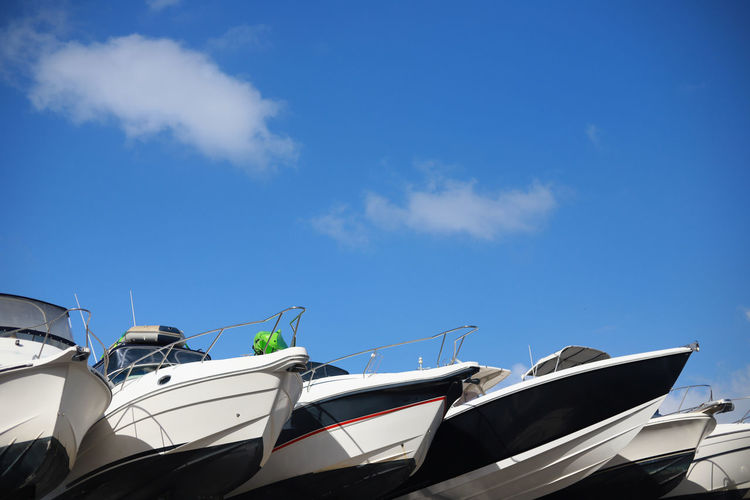 Low Angle View Of Boats Moored Against Blue Sky