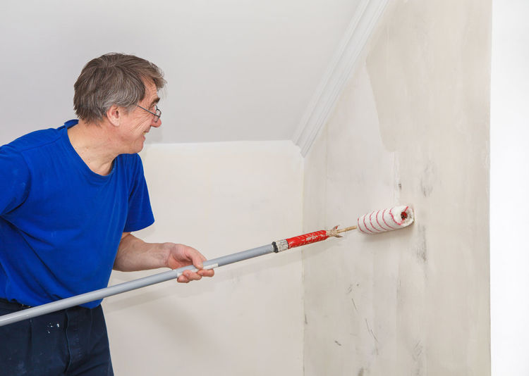 Mature painter using roller on wall