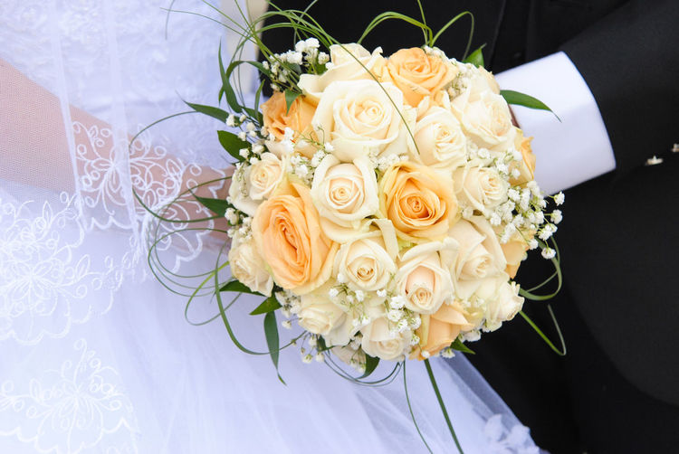 Midsection Of Bride And Groom Holding Bouquet During Wedding