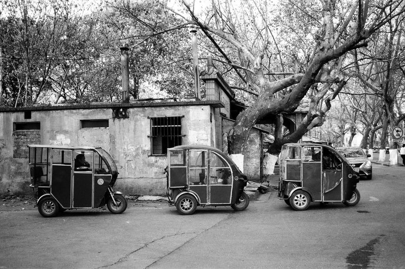 Three musketeers. Leica M6 Fomapan100 Streetphotography Film Photography Blackandwhite Bnw Building Exterior Built Structure Architecture Tree Land Vehicle Building Mode Of Transportation City No People Street Stationary Cart