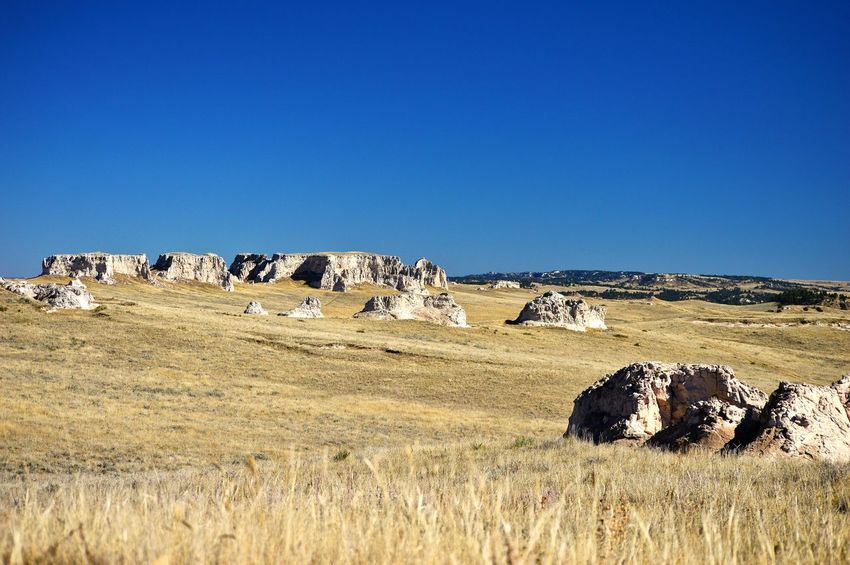 Pasture of rocks Bluesky Many Of A Kind West Of Lusk Wyoming Grass In The Distance. Outdoors Sunshine Blue Color Rock Formations Shadows Pasture Rural Scene Landscape