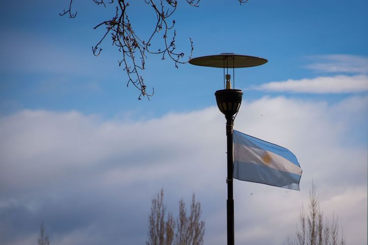 An Argentinian flag moves with the wind, in El Calafate, Santa Cruz, Argentina. Cloud - Sky Day Horizontal Low Angle View Nature No People Outdoors Sky Tree