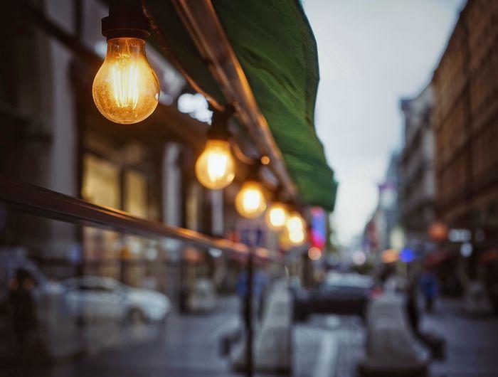 Low angle view of illuminated light bulbs on street