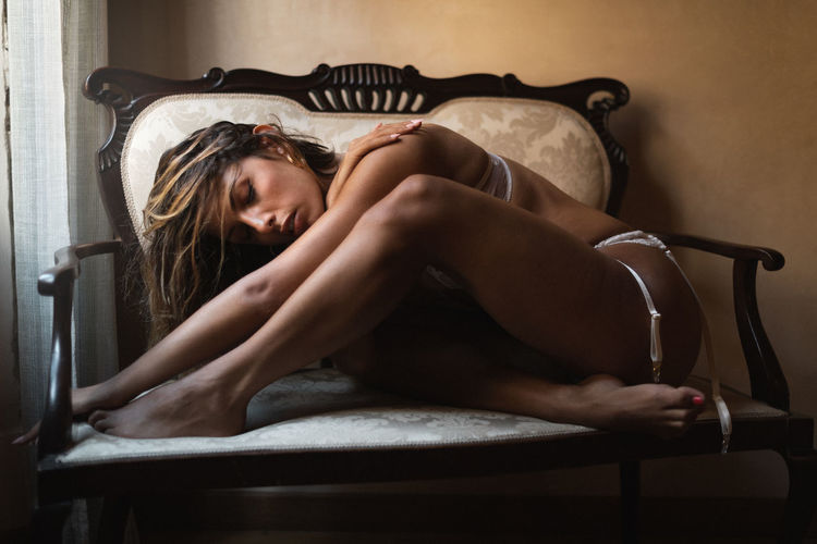 Seductive woman sitting on couch