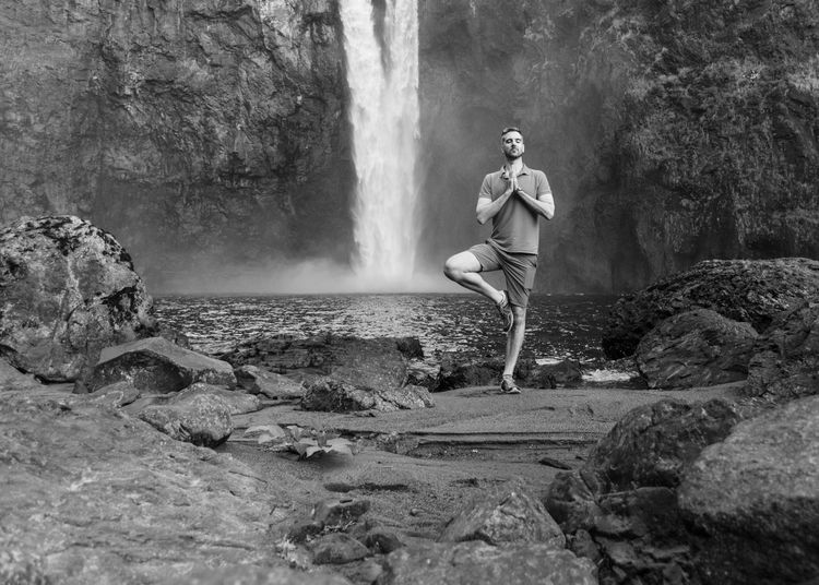 Man doing tree yoga pose near waterfall in black and white. Meditation Nature Yoga Adult Casual Clothing Forest Full Length Health Leisure Activity Lifestyles Mental Health  Mid Adult Nature One Person Outdoors Real People Rock Rock - Object Solid Standing Tree Tree Pose Water Waterfall Young Adult