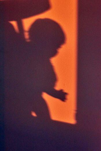 Shadow of woman on orange wall