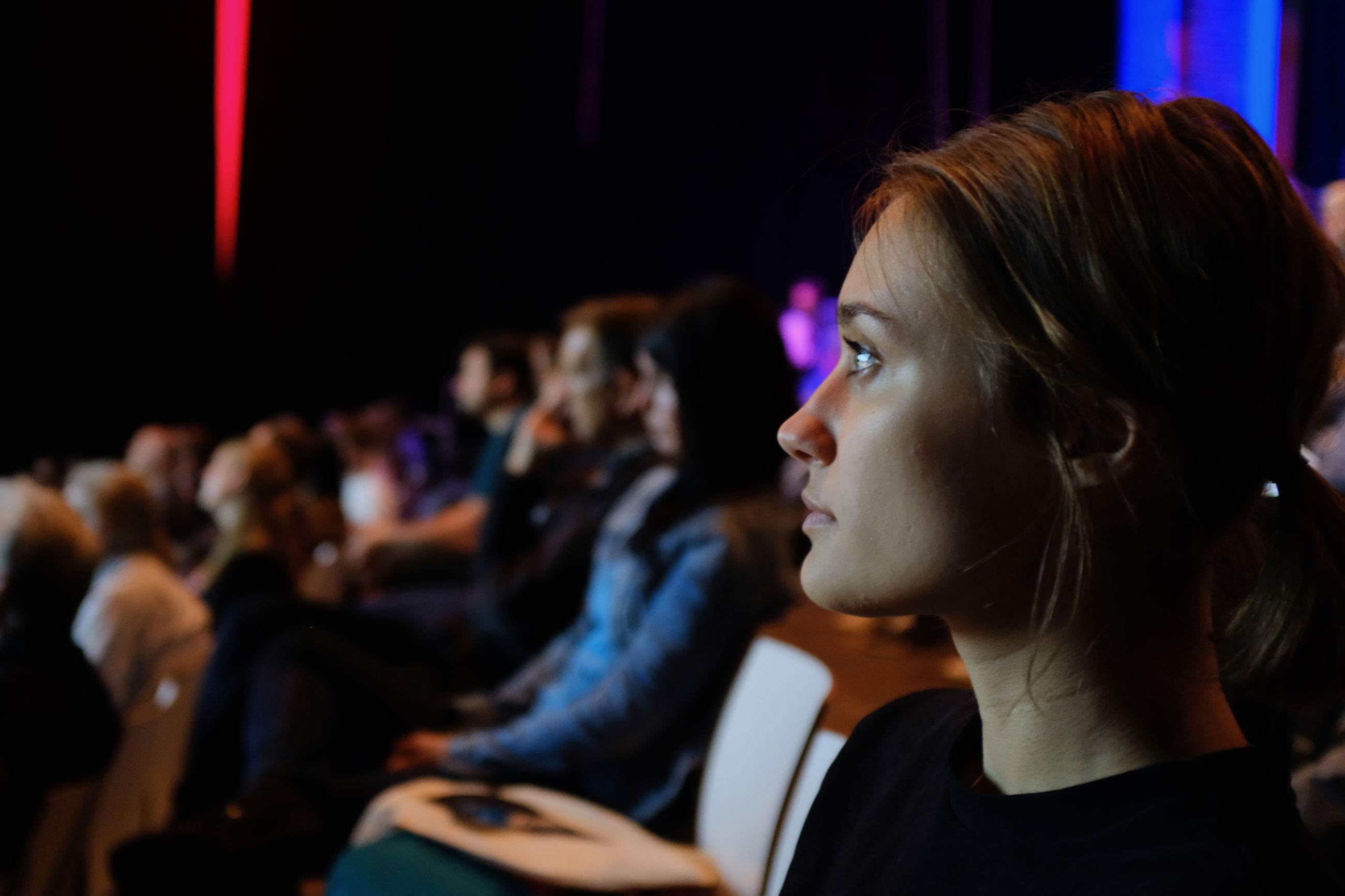 real people, focus on foreground, indoors, young adult, young women, audience, side view, headshot, women, large group of people, sitting, illuminated, close-up, day, adult, people