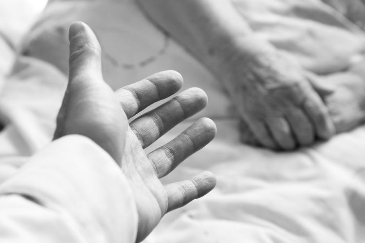 Cropped Hand Against Senior Woman Lying On Bed