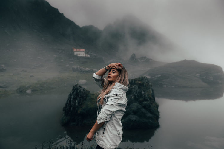 Young woman standing outdoors during foggy weather