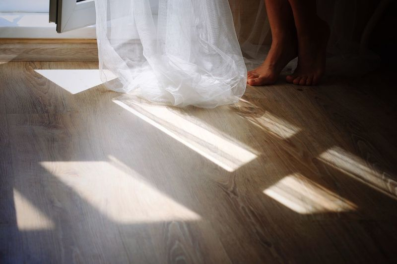 Low section of woman with dress on hardwood floor