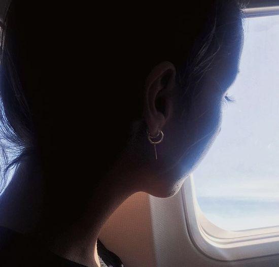 Portrait of woman seen through airplane window