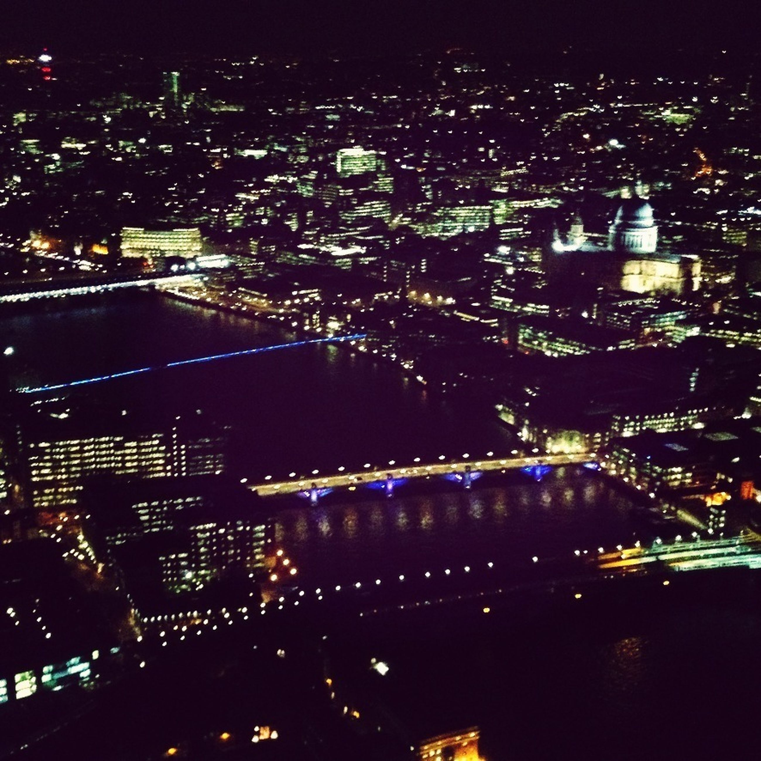 illuminated, night, city, cityscape, building exterior, architecture, built structure, high angle view, skyscraper, crowded, city life, road, office building, modern, aerial view, capital cities, tall - high, tower, street, transportation