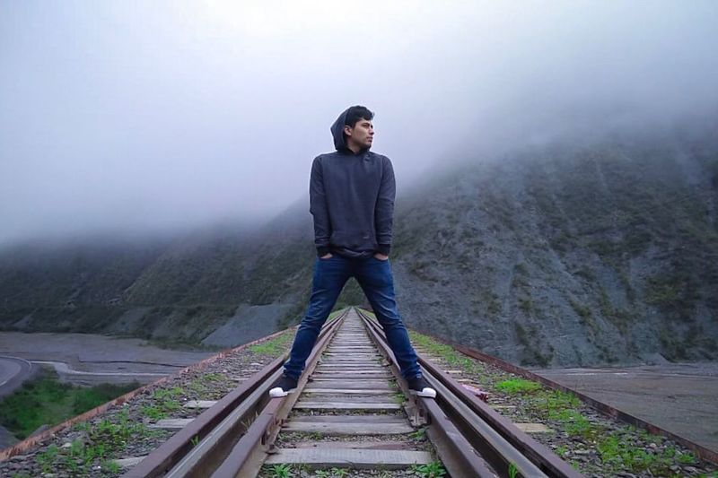 Full length of man standing on railroad track during foggy weather