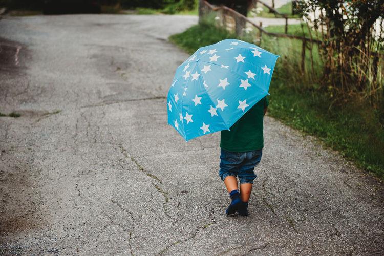 Full length rear view of woman walking in rain