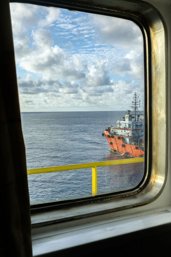 window Oil Field Frame Glass Offshore Offshore Life Horizon Oil And Gas Industry Ship Vessel Tug Boat Sea Ocean Cloudy Day Water Sea Looking Through Window Nautical Vessel Sky Close-up Horizon Over Water