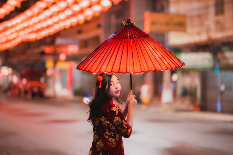 Portrait of woman with red umbrella standing against illuminated wall