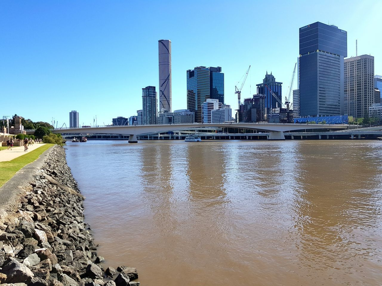 architecture, skyscraper, building exterior, built structure, city, tall - high, water, modern, downtown district, urban skyline, tower, day, sky, travel destinations, outdoors, financial district, cityscape, clear sky, tree, no people, nature