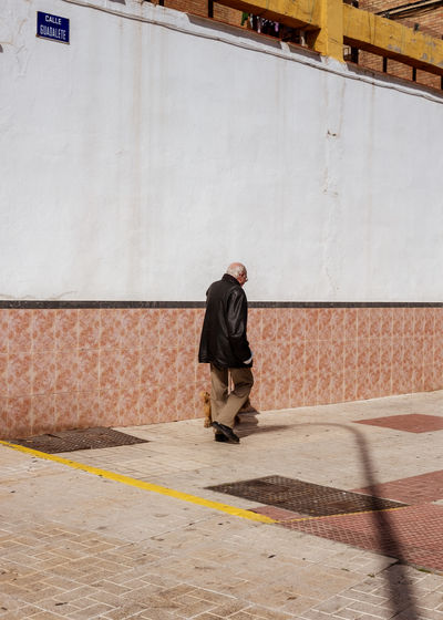 Man walking on footpath against wall