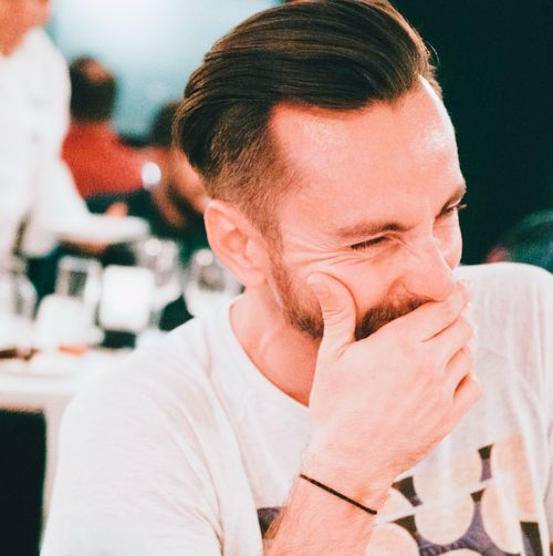 Close-Up Of Man Laughing While Covering Mouth In Restaurant