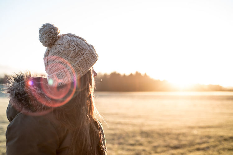 Woman wearing hat against sun during sunset