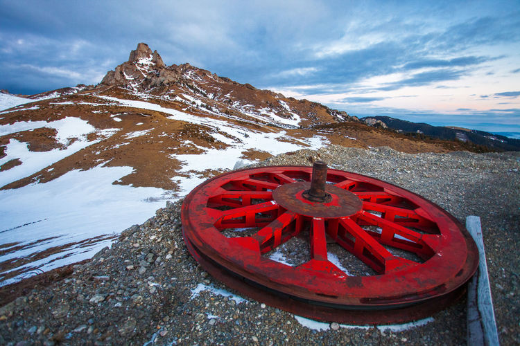 Close-up of red wheel against snowcapped mountain