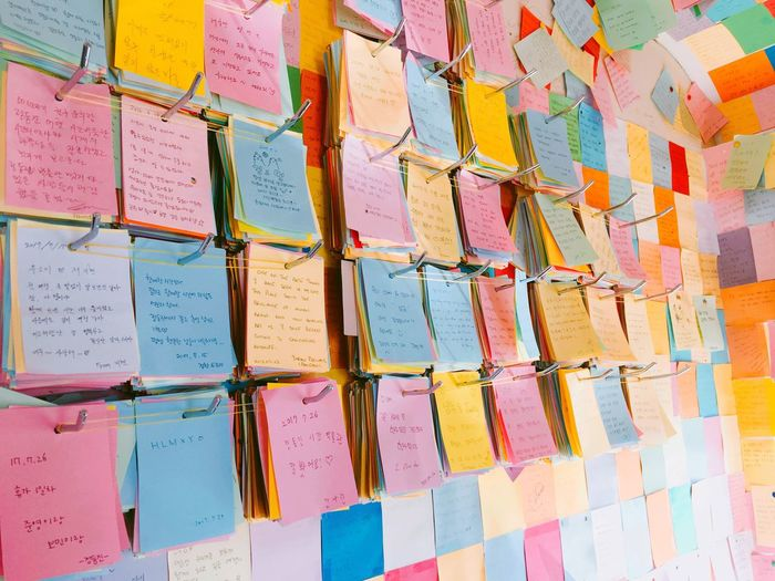 Colorful adhesive notes hanging on metal