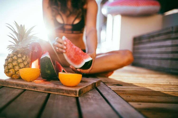 Midsection Of Woman Having Fresh Fruits While Sitting On Wooden Floor