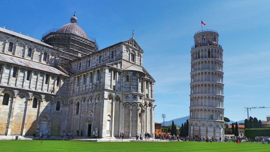 Piazza dei miracoli by leaning tower of pisa against sky