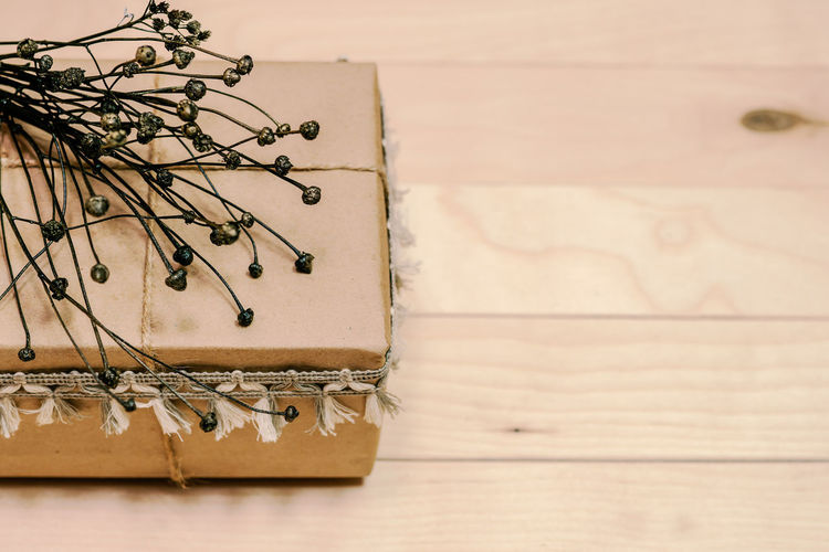 High angle view of gift box with dried plant on wooden table
