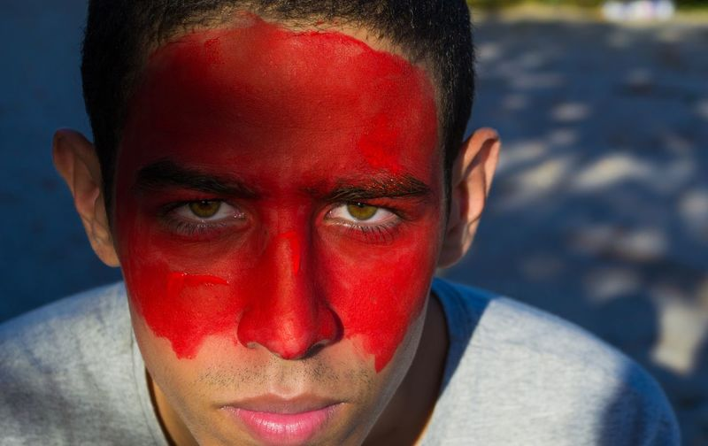 Close-Up Portrait Of Young Man With Red Face Paint