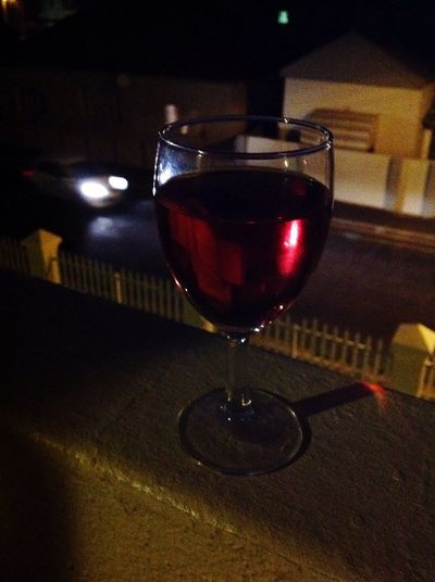 Wine Moments Glass Of Rosé Glass Of Wine On The Wall Cool Summer Evening Car Passing By Street Below Grainy Picture.