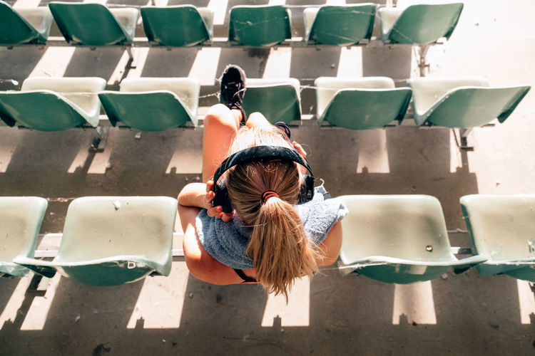 Top view of athlete sitting at an old stadium listening to music and resting after exercising