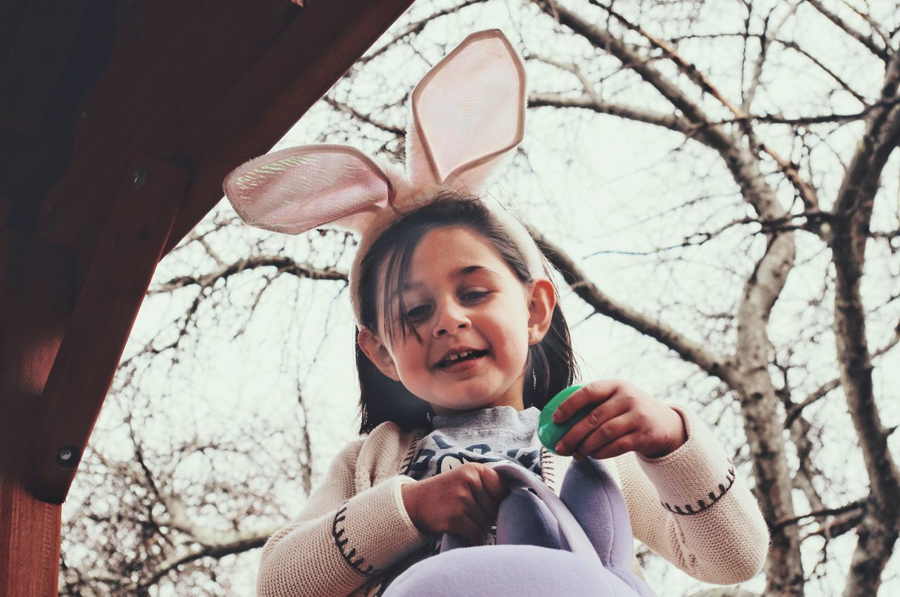 Low angle view of girl holding easter egg by bare tree